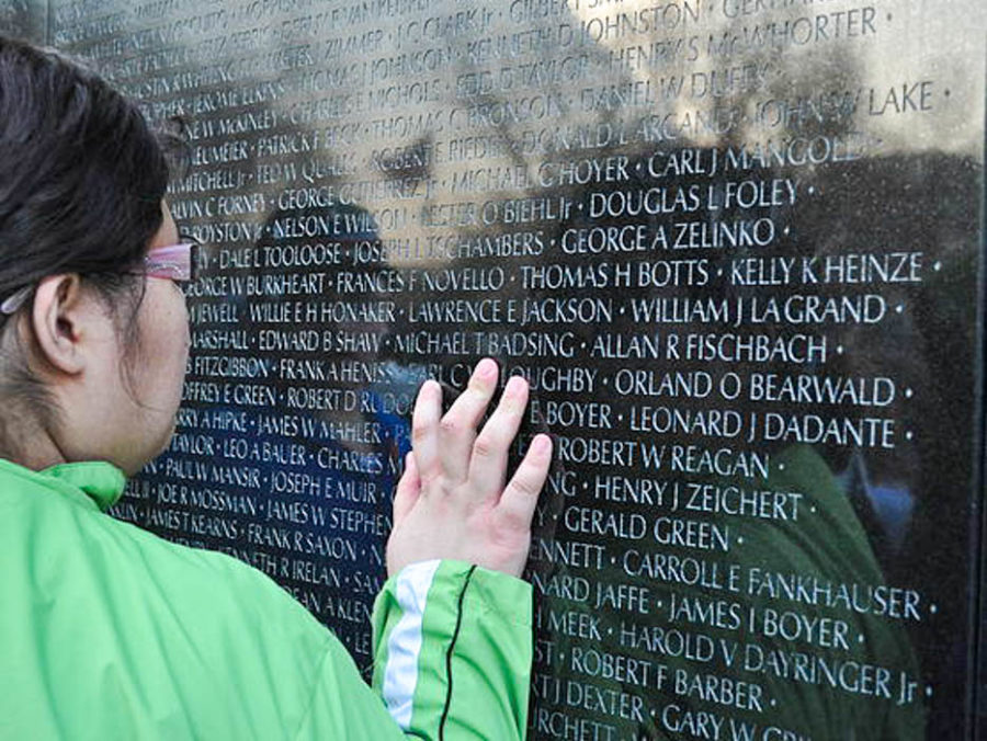 Student touching monument with names etched into it.