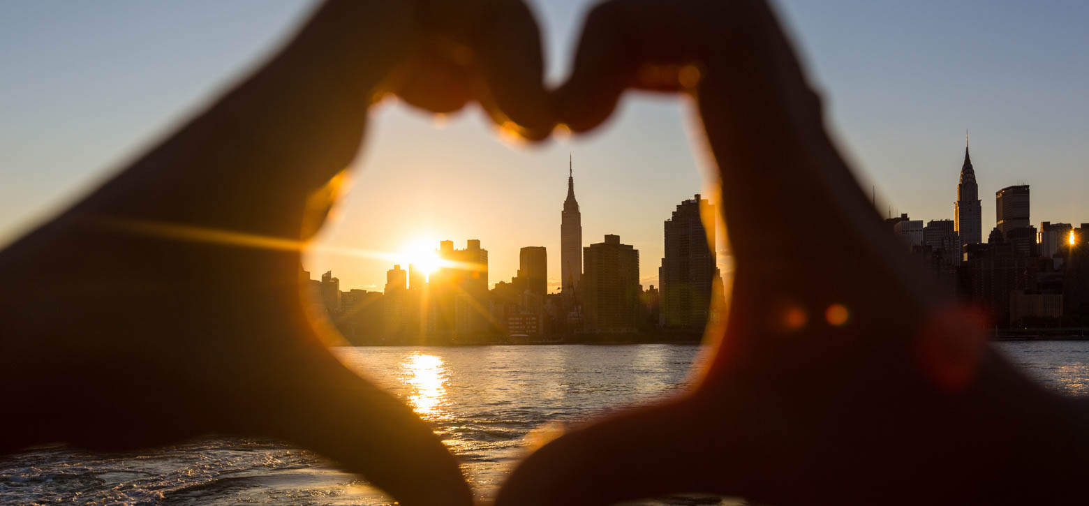 Hands making a heart with the NYC skyline in the middle
