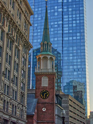 Old clocktower among skyscrapers