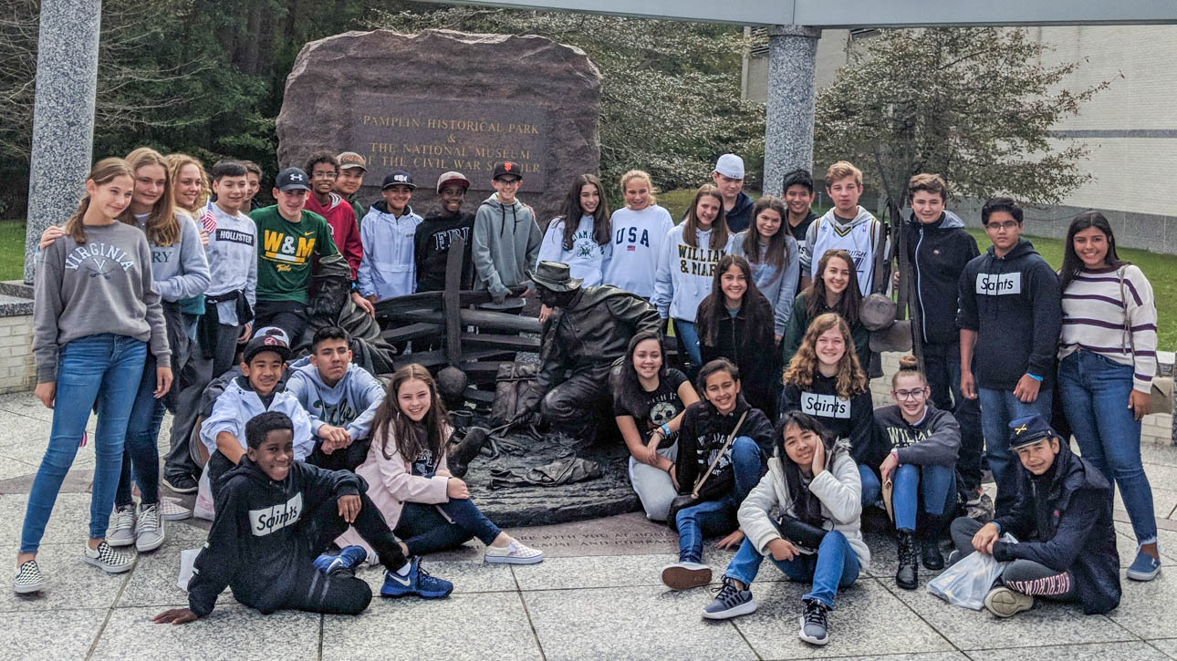 Group of students in front of a monument in Colonial Williamsburg