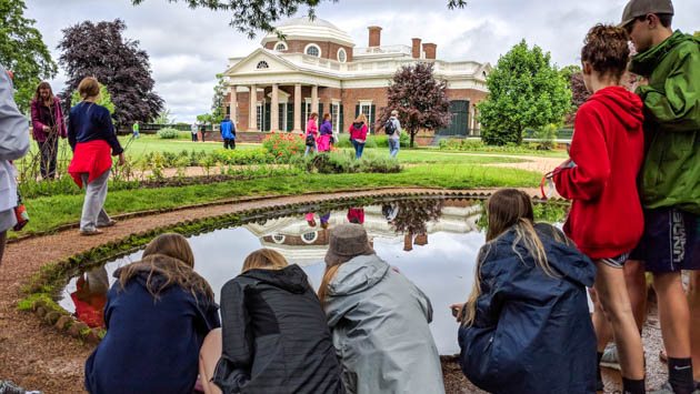 Students crouching by a pond outside of Monticello