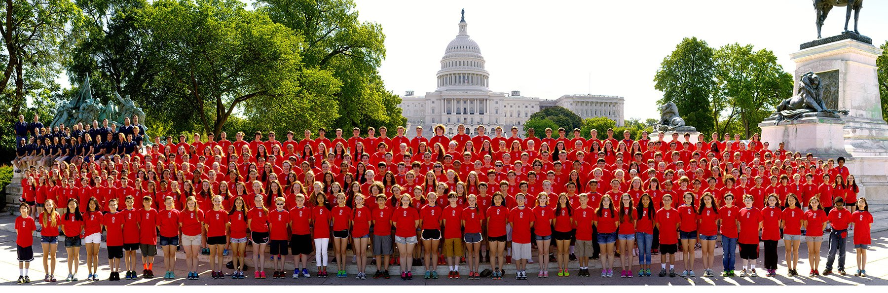 Large tour group all in red shirts taking a group photo outside of the capitol building