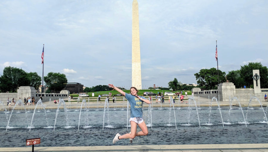 Girl jumping in the air in front of the Washington monument