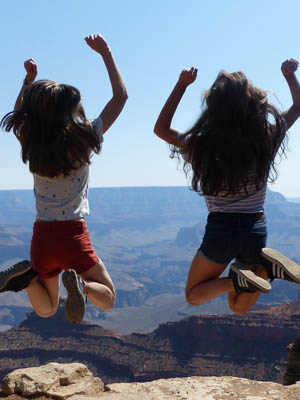 Two girls jumping in the air with the Grand Canyon in the background