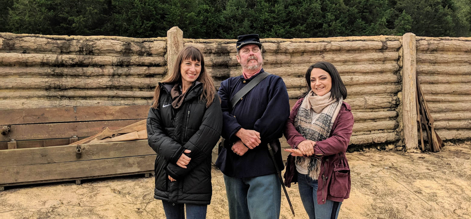 Two teachers posing with a reenactor