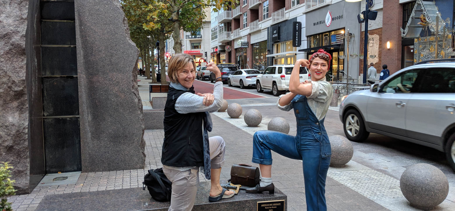 Teacher flexing her bicep with Rosie the Riveter Statue